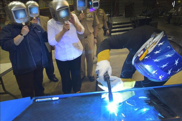 A welder authenticates the keel by welding the initials of the ship's sponsor onto the keel plate of the future USS Billings (LCS 15), in a ceremony held at Fincantieri Marinette Marine in Marinette, Wisconsin. (Photo by Lockheed Martin)