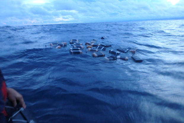 Crew members on an interceptor boat from the Coast Guard Cutter Valiant approach bales of cocaine jettisoned in the Eastern Pacific Ocean by suspected smugglers, May 22, 2017. (U.S. Coast Guard photo)