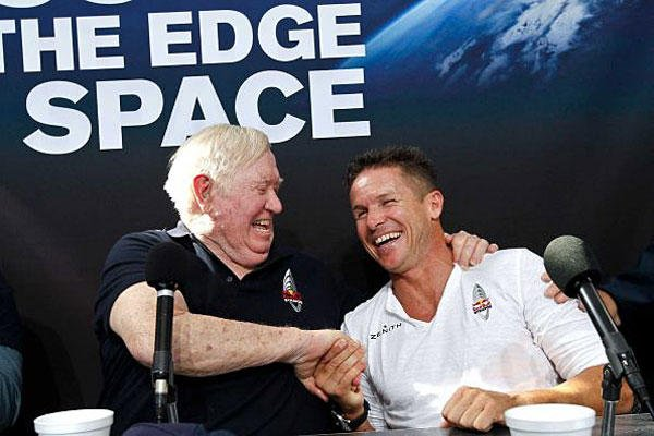 Felix Baumgartner, right, of Austria, shares a laugh with Col. Joe Kittinger, USAF retired, after successfully jumping from a space capsule lifted by a helium balloon at a height of just over 128,000 feet above the Earth's surface.