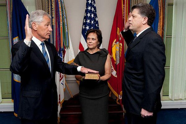 Chuck Hagel, left, is sworn into office as the 24th defense secretary by Michael L. Rhodes, the Defense Department's director of administration and management, as Hagel's wife, Lilibet, holds a Bible at the Pentagon, Feb. 27, 2013.