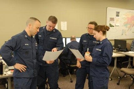 Members of the Coast Guard Sector Anchorage, Alaska, Incident Management Team for the Alaska Shield 2014 exercise examine data during a morning meeting March 31, 2014.