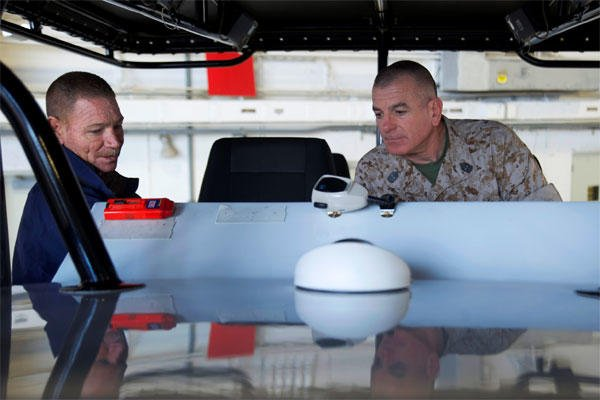 Marine Corps Sgt. Maj. Bryan B. Battaglia, right, senior enlisted advisor to the chairman of the Joint Chiefs of Staff, explores the instrument panel of the Midnight Express, a tactical training boat.