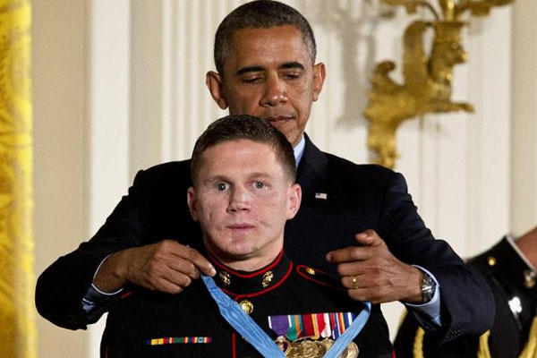 "President Barack Obama awards retired Marine Cpl. William ""Kyle"" Carpenter, the Medal of Honor for conspicuous gallantry, Thursday, June 19, 2014, during a ceremony in the East Room of the White House in Washington. (AP Photo/Jacquelyn Martin)"