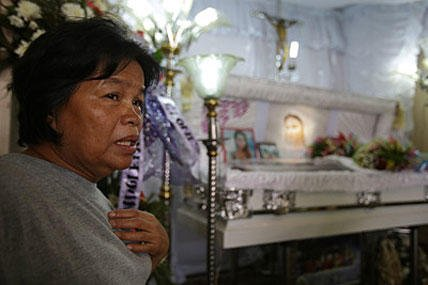 In this Oct. 17, 2014, photo, Julita Laude, mother of Filipino transgender Jennifer Laude, grieves beside the casket of her daughter at a funeral parlor in Olongapo, Zambales province, northern Philippines. Aaron Favila/AP