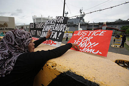 In this Oct. 18, 2014, photo, activists place slogans during a rally near the USS Peleliu, where U.S. Marine Pfc. Joseph Scott Pemberton is being held for allegedly killing Filipino transgender Jennifer Laude, at the Subic Bay free port. Aaron Favila/AP
