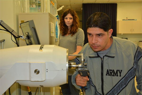 Army 1st Lt. John Arroyo works on strengthening his right hand while his occupational therapist, Katie Korp, looks on at the Center for the Intrepid, Brooke Army Medical Center's rehabilitation facility, Jan. 16, 2015. (U.S. Army photo/Robert Shield)