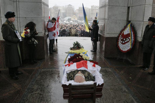 People pay their respects to the body of serviceman Thomas Sukhiashvili, a Georgian national who was killed in fighting against Russian-backed separatists, during a commemoration ceremony in Kiev, on Wednesday, Jan. 21, 2015. (AP Photo/Efrem Lukatsky)