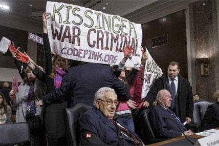 Protesters interrupt the start of a Senate Armed Services hearing, on Capitol Hill, Thursday, Jan. 29, 2015, as they shout at former Secretary of State Henry Kissinger, center. (AP Photo/J. Scott Applewhite)