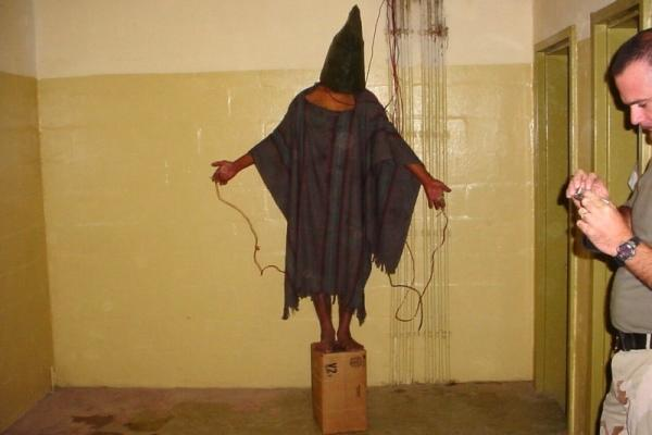 This late 2003 photo obtained by The Associated Press shows an unidentified detainee standing on a box with a bag on his head and wires attached to him in the Abu Ghraib prison in Baghdad, Iraq. Stars and Stripes