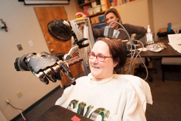 Jan Scheuermann, who has quadriplegia, brings a chocolate bar to her mouth using a robot arm she is guiding with her thoughts. (Photo by University of Pittsburgh Medical Center)