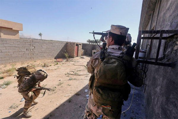 In this Sunday, April 26, 2015 photo, Iraqi security forces clash with Islamic State group militants, during an operation to retake the water control station on a canal lost over the weekend, in the town of Garma.  (AP Photo)