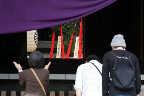 Religious offerings dedicated by Japanese Prime Minister Shinzo Abe are seen, center background, as people pray at the Yasukuni Shrine in Tokyo during an annual spring festival on Tuesday, April 22, 2015. (KOJI UEDA/AP)