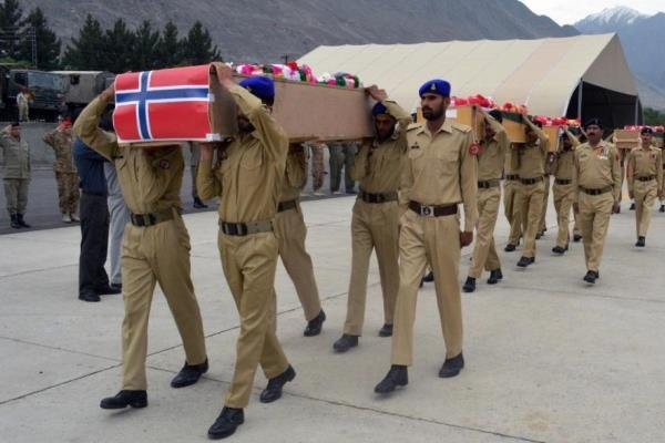 Pakistani soldiers carry the caskets of victims of a helicopter crash to a military plane prior to their transport to Islamabad. (AP Photo/M. Hussain)