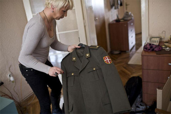 Helena, a transgender person, holds her Serbian army uniform Wednesday, April 15, 2015, at her friend's apartment in Belgrade, Serbia. Maj. (AP Photo/Marko Drobnjakovic)