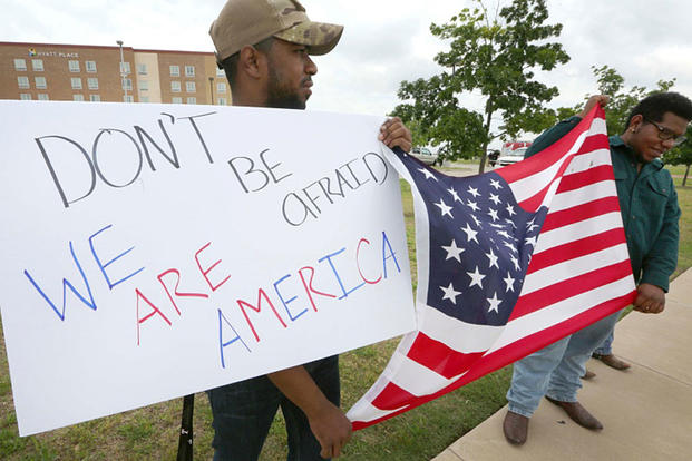 Joseph Offutt, left, and Raheem Peters hold a sign and a U.S. flag across the street from the Curtis Culwell Center, Tuesday, May 5, 2015, in Garland, Texas. LM Otero/AP