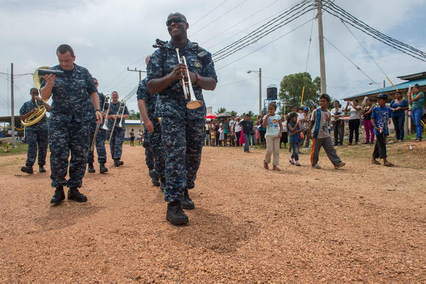 U.S. Navy Petty Officer 2nd Class Vincent Moody and other members of the U.S. Fleet Forces Band ensemble Uncharted Waters walk with area residents in Puerto Cabezas, Nicaragua, May 22, 2015. (U.S. Navy photo/Petty Officer 2nd Class Brittney Cannady)