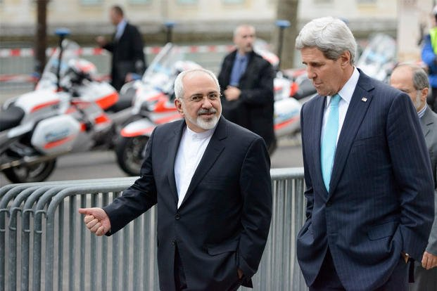In this file photo taken Jan. 14, 2015, U.S. Secretary of State John Kerry speaks with Iranian Foreign Minister Mohammad Javad Zarif, as they walk in Geneva, Switzerland, ahead of the next round of nuclear discussions. (Laurent Gillieron/Keystone via AP)