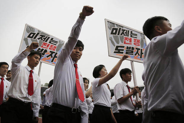 "People pump their fists in the air and chant ""Defend!"" as they carry placards with propaganda slogans that read: ""American Imperialists are the war aggressor"" during the ""Pyongyang Mass Rally on the Day of the Struggle Against the U.S."" Wong Maye-E/AP"