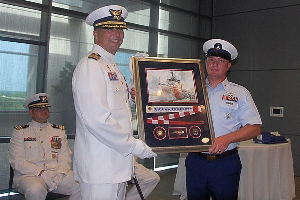 Cutter Diligence former commanding officer Capt. Jeffrey Randall receives a parting gift of a framed painting with a commissioning pennant and three unique coins. (U.S. Coast Guard photo)