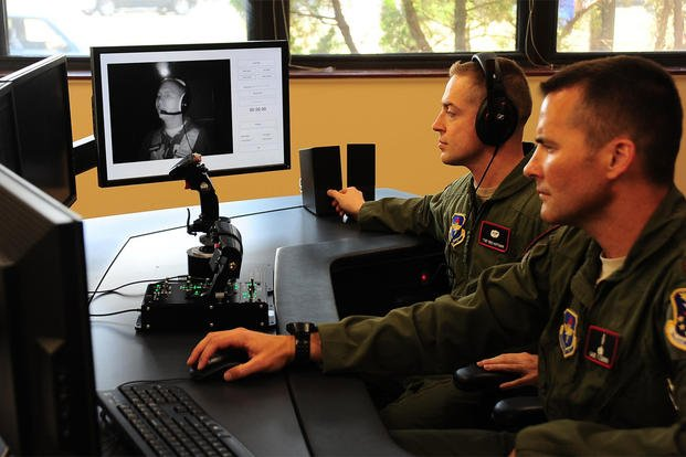 Tech. Sgt. Benjamin Hoffman and Maj. Michael Fleming monitor Col. James Fisher on the video feed from the cockpit of the new spatial disorientation simulator Aug. 5, 2015, at Columbus Air Force Base, Miss. (U.S. Air Force photo/Airman 1st Class John Day)