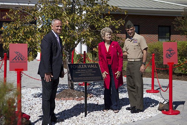 Betsy Fowler, widow of Col. James Fowler founder of the Marine Corps Marathon, poses with guests after unveiling the plaque at the Marine Corps Marathon building dedication at Marine Corps Base Quantico, Virginia. (U.S. Marine Corps/Sgt. Melissa Karnath)