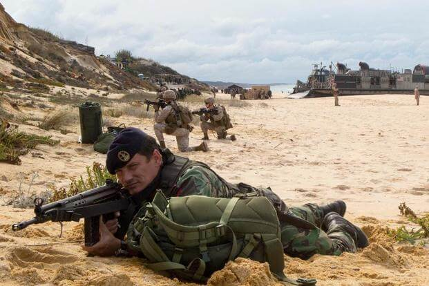 A Portuguese Marine holds security at Pinheiro Da Cruz, Praia Da Raposa beach, Portugal, while participating in a combined amphibious assault exercise, Oct. 20, 2015, during Trident Juncture 15. (Photo by: Sgt. Austin Long)