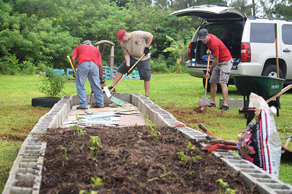 Airmen assigned to the 554th RED HORSE Squadron expand a garden Sept. 26, 2015, at the Guma San Jose Homeless Shelter in Dededo, Guam. (U.S. Air Force/Senior Airman Joshua Smoot)
