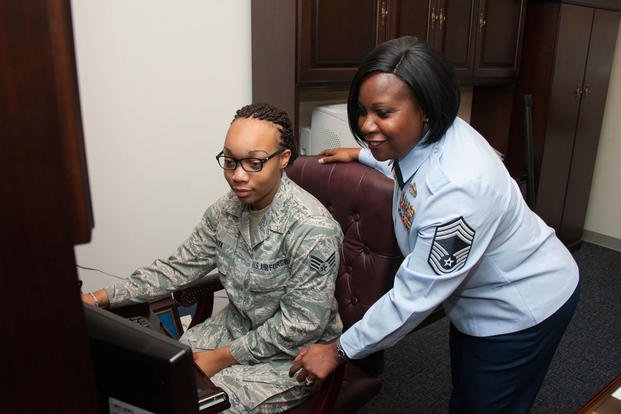 Chief Master Sgt. Yolanda Jennings works on a project with Senior Airman Jameka Ruta, Oct. 14, 2015. Jennings is a breast cancer survivor. (Photo: Melanie Rodgers Cox)