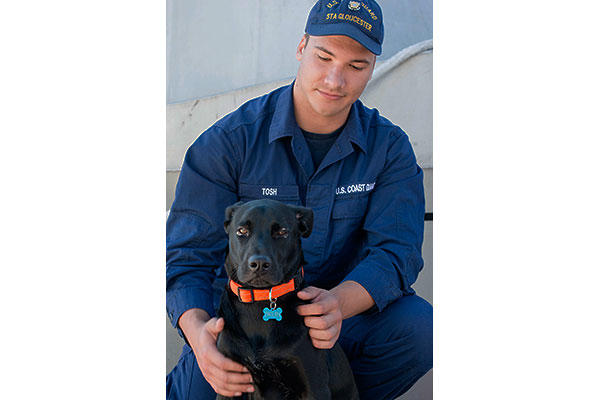 Fireman Nicholas Tosh and Bruin pose for a photo at Coast Guard Station Gloucester, Mass., Wednesday, Nov. 4, 2015. (U.S. Coast Guard/PO2 Cynthia Oldham)