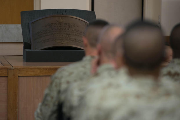 A plaque dedicated to 2nd Lt. Walter V. Brown sits in front of candidates of Officer Candidate School learning about Marine officer history at Marine Corps Base Quantico, Virginia, Nov. 20, 2015. (Photo: Sgt. Eric Keenan)