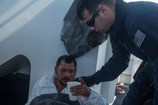 A Coast Guard law enforcement official aboard the Coast Guard Cutter Kathleen Moore provides water to a Cuban man, in the Florida Straits, Dec. 9, 2015. (Photo: Petty Officer 3rd Class Ashley J. Johnson)