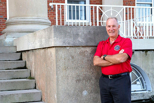 Kevin Scott, manpower, personnel and training lead for Combat Support Systems at Marine Corps Systems Command, stands in front of the command's headquarters building aboard Marine Corps Base Quantico, Virginia. (U.S. Marine Corps/Mathuel Browne)
