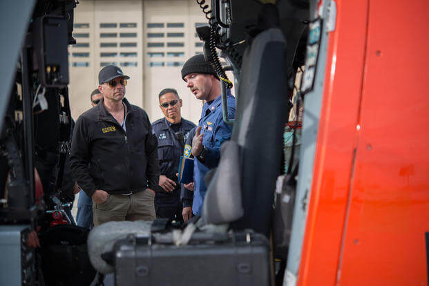 A Coast Guard member explains the features of a MH-65 Dolphin helicopter to K-9 teams at Coast Guard Air Station San Francisco, Wednesday, Dec. 2, 2015, to prepare for Super Bowl 50. (Photo: Petty Officer 3rd Class Loumania Stewart)
