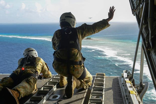 Australian Army Cpl. Teome Matamua and Sgt. Phillip McIllvaney wave to islanders in the Federated States of Micronesia after delivering donated goods and critical supplies during Operation Christmas Drop. (Photo: Staff Sgt. Katrina Brisbin)