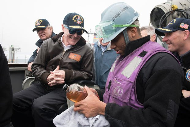 Secretary of the Navy Ray Mabus receives a fuel sample of alternative fuel from Gas Turbine Systems Technician (Mechanical) 3rd Class Shalen Shivers. (Photo: Mass Communication Specialist 2nd Class Armando Gonzales)