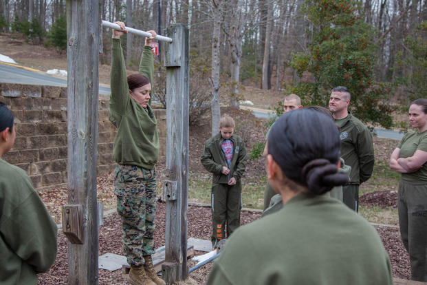 Major Misty Posey, center, demonstrates proper form for pull-ups to Marines at Marine Corps Base Quantico, Virginia, Feb. 19, 2016. (Photo: Sgt. Dylan Bowyer)