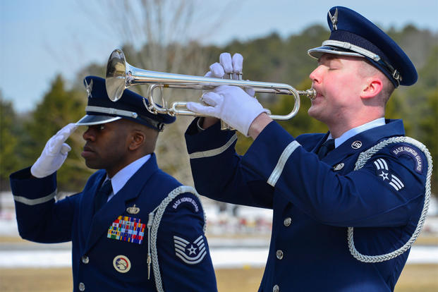"Tech. Sgt. Isaiah Martin, Dover Air Force Base Honor Guard NCO in charge, salutes as Senior Airman Gene Kellenberger, Dover AFB Honor Guard member, plays ""Taps"" during a funeral Feb. 25, 2015. (U.S. Air Force photo/Airman 1st Class Zachary Cacicia)"
