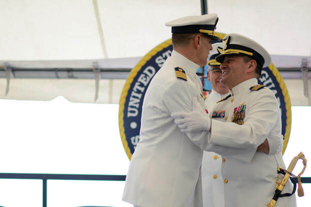 Capt. Anthony Ceraolo (right), new commanding officer of Sector San Francisco, salutes and hugs Capt. Greg Stump (left) during a change of command ceremony in San Francisco, Tuesday July 19, 2016. (Photo: Petty Officer 3rd Class Adam Stanton)