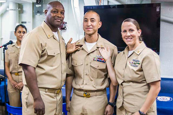 GSEC Alexis Ortiz, center, receives his chief petty officer (CPO) anchors from ITC Larry Ward and ISC Shauntel Moon after being promoted aboard the USS Stethem (DDG 63). (U.S. Navy/Ensign Rebecca Speer)