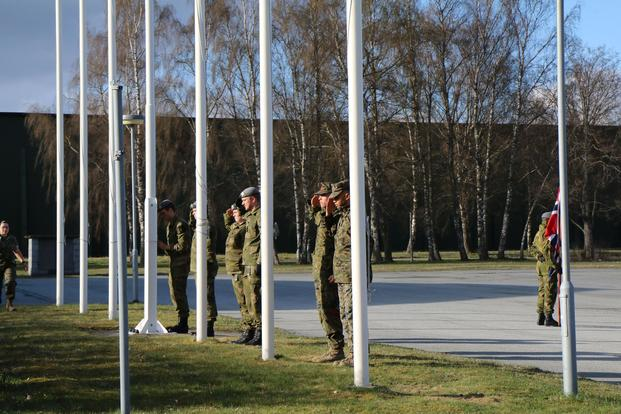 Marines and Norwegian soldiers salute their respective flags during a V-E Day ceremony at Vaernes Garrison, Norway, on May 8, 2017. Hope Hodge Seck/Military.com