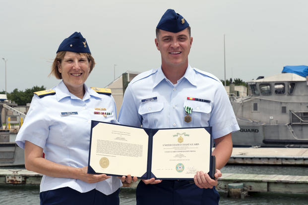 Coast Guard Rear Adm. Meredith Austin poses with Fireman James Sanders after presenting him with the Coast Guard Commendation Medal at Coast Guard Sector Field Office Fort Macon, May 31, 2017. (U.S. Coast Guard/Corinne Zilnicki)