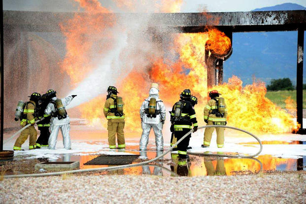 Service members with the Peterson Air Force Base Fire Department conduct live training with the Cimarron Hills Fire Department July 21, 2014, at a special training facility on Peterson AFB, Colo. (U.S. Air Force photo/Michael Golembesky)