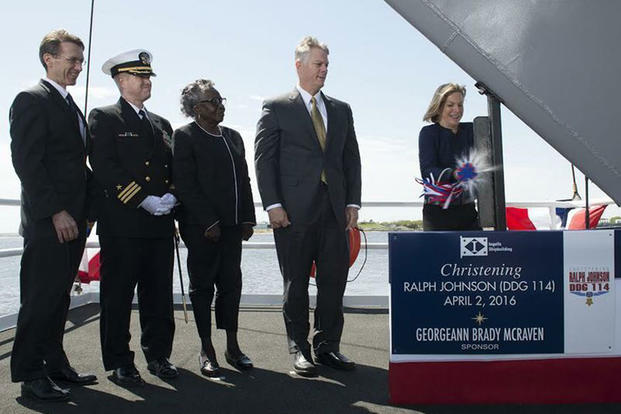 Ship Sponsor Georgeann McRaven ceremoniously breaks a bottle of champagne on the bow during the christening ceremony for the future guided missile destroyer USS Ralph Johnson, April 2, 2016. (U.S. Navy photo courtesy of Huntington Ingalls Industries)