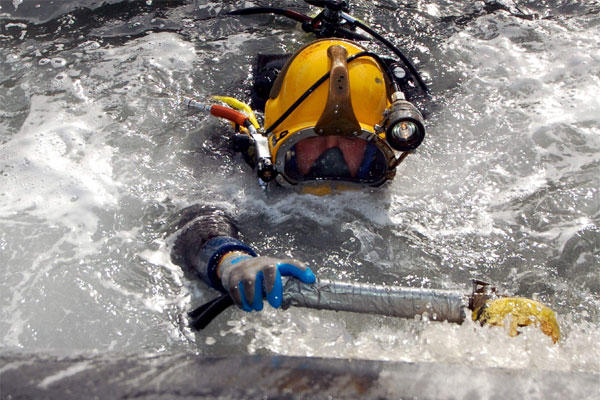 A U.S. Navy diver uses a scrubber to clean the hull of the Key West
