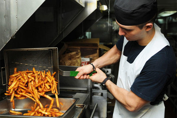 Culinary Specialist 3rd Class Jose Gomez transfers french fries in preparation for chow in the chiefs' mess of the USS Abraham Lincoln (CVN 72).. (U.S. Navy photo by Mass Communication Specialist Seaman Zachary S. Welch)