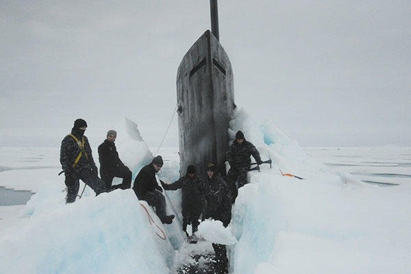 Sailors aboard the fast attack submarine USS Seawolf (SSN 21) remove Arctic ice from the hull after surfacing at the North Pole. (U.S. Navy)