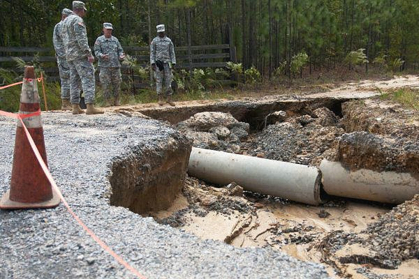 North Carolina National Guardsmen assigned to the 505th Engineer Battalion's 882nd Engineer Company, assess the damage to a road in Eastover, S.C., Oct. 13, 2015. (North Carolina Army National Guard/Sgt. Brian Godette.)