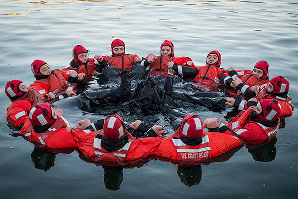 Crew members from the Coast Guard Cutter Spencer leak-test their survival suits in chilly Boston Harbor Nov. 18, 2015. As air and water temperatures drop, the Spencer crew are preparing for the approaching winter. (U.S. Coast Guard/PO3 Ross Ruddell)