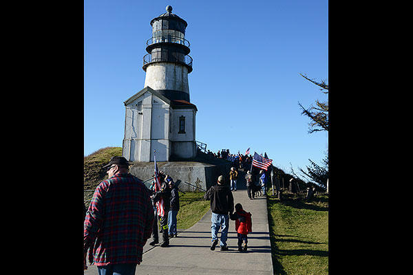 Volunteers, service members and families gather at the Cape Disappointment lighthouse for a memorial ceremony honoring the Coast Guardsmen and fishermen who perished along the Columbia and Quillayute River bars. (U.S. Coast Guard/PO3 Jonathan Klingenberg)
