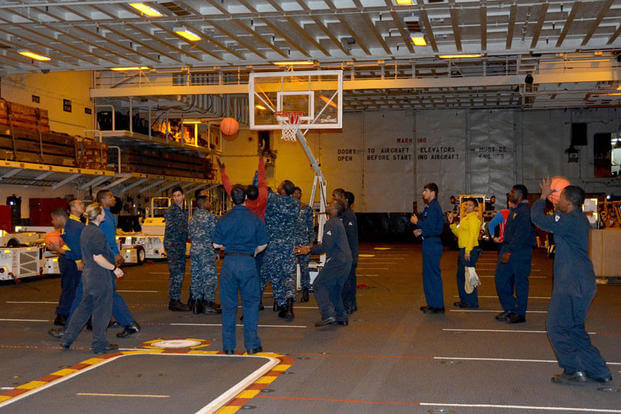Sailors shoot basketballs in the hangar bay of the amphibious assault ship USS Peleliu  prior to an MWR-sponsored three-point shootout contest while the NCAA March Madness men's basketball tournament is displayed for the crew. Dustin Knight/Navy